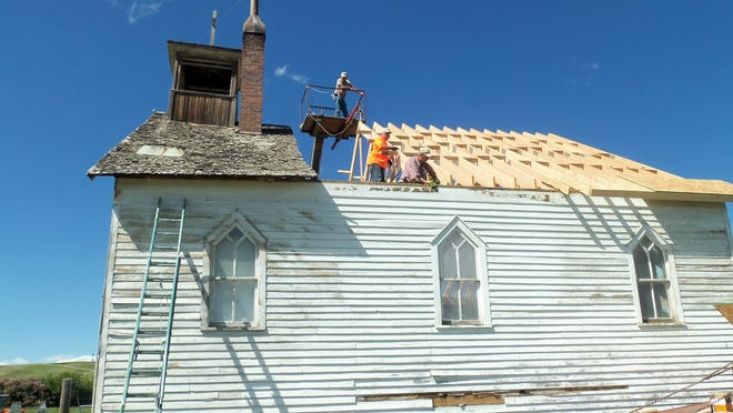 Volunteers work to replace the roof of Sacred Heart Church east of Valier during the summer of 2013.