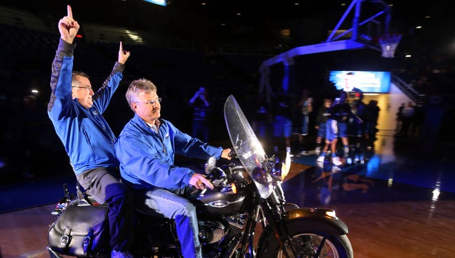 MTSU women's basketball coach Rick Insell enters the Murphy Center arena on the back of a motorcycle driven by Tom Bumpus, owner of Bumpus Harley-Davidson of Murfreesboro, during the Murphy Madness.