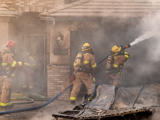 Visalia Firefighters respond to a garage fire in the 2100 block of North Duke Street on Monday, October 29, 2018.