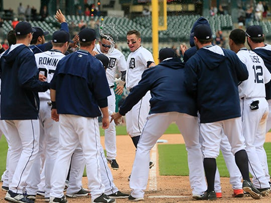 James McCann, center, is greeted at home by a pack of Tigers after his homer in the 11th inning.