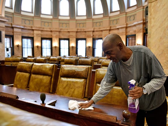 Mississippi House of Representative porter William Bennett polishes desks in advance of the opening day of the Mississippi legislative session Tuesday.