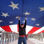 Air Force veteran Al Gonzalez helps keep the flag off the ground as it's launched up the flagpole Wednesday in Northeast El Paso. See a gallery from the parade at elpasotimes.com.