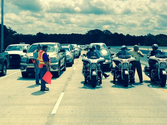 Police on motorcycles prepare to lead traffic across the southbound spans of the Curtis-Coleman Memorial Bridge on Tuesday morning following a dedication ceremony. All four lanes of the bridge and approaches were to be opened by Tuesday afternoon.