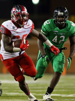 Oct 15, 2015; Denton, TX, USA; Western Kentucky Hilltoppers running back Anthony Wales (20) runs by North Texas Mean Green defensive end Chad Polk (42) during a game at Apogee Stadium. Western Kentucky won 55-28. Mandatory Credit: Ray Carlin-USA TODAY Sports