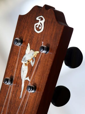Gordy Bischoff displays details of his hand-crafted ukulele, including inlays of mother of pearl at his workshop south of Eau Claire, WI. Bischoff's wife sketched and designed this figure of a fairy holding a ukulele.
