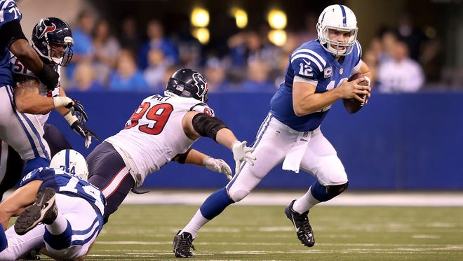 Indianapolis Colts quarterback Andrew Luck (12) escapes from the rushing Houston Texans defensive end J.J. Watt (99) in the second half of their game Sunday, December 14, 2014, afternoon at Lucas Oil Stadium. The Colts defeated the Texans 17-10 to win the AFC South.