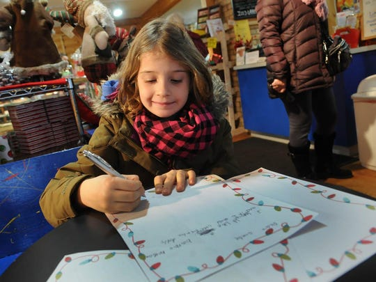 Julia Kubera of Chicago writes a letter to Santa at Double Delites during last year's children's Elf Hunt, part of Egg Harbor's Holly Days.