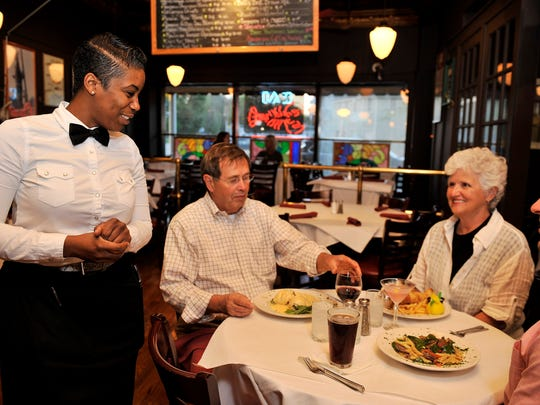 Server Sierra Hill checks on the table with Art, left, and Sally Thompson of Grosse Pointe Park and their grandson, Zachary Fragoso of Detroit.