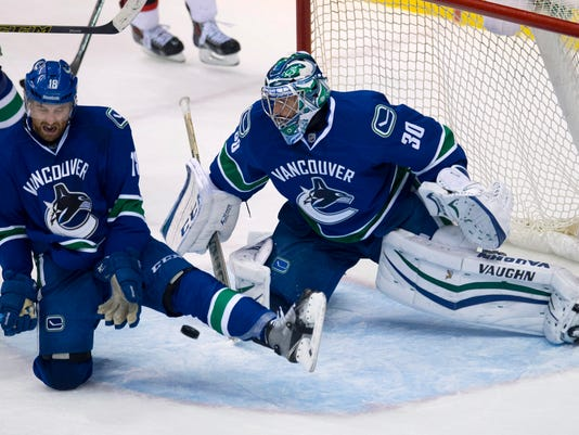 Vancouver Canucks defenseman Ryan Stanton (18) stops a shot as goalie Ryan Miller looks on during the third period of an NHL hockey game, Tuesday, Nov. 25, 2014 in Vancouver, British Columbia.  (AP Photo/The Canadian Press, Jonathan Hayward)