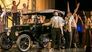 """Coalhouse Walker Jr. (Jowon Briggs) celebrates his purchase of a Model T with Henry Ford's factory workers in Walnut Hills High School's production of """"Ragtime."""""""