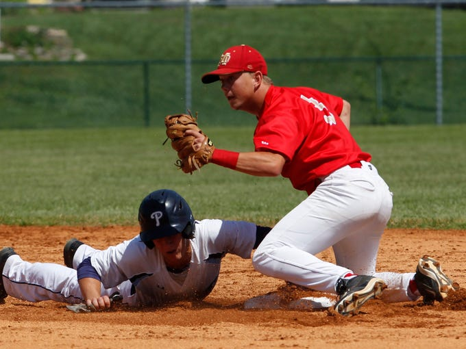 Providence High School's Parker Graf (7) dives back to second base safe under the tag of Mater Dei High School's Jake Fleming (3) in the  2014 IHSAA Class 2A Regional Championships at Providence High School in Clarksville, Indiana, June 2, 2014.