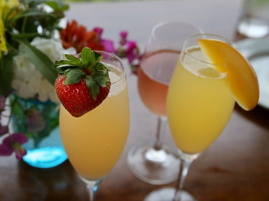 A strawberry and apricot mimosa, front left and right, and cocktail special of Dry Rosé and Chardonnay Champagne, back center, served with lunch at  Hunt Country Vineyards, during their food crawl around Keuka Lake in the Finger Lakes on Monday, Aug. 7, 2017.