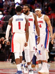 Pistons guard Reggie Jackson celebrates with center