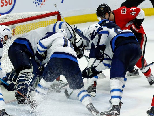 Ottawa Senators' Jean-Gabriel Pageau (44) tries to jam the puck past Winnipeg Jets goaltender Connor Hellebuyck (37) during third period NHL hockey action in Ottawa, Sunday Feb. 19, 2017. (Fred Chartrand/The Canadian Press via AP)