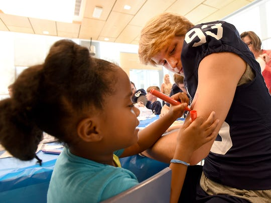 Five-year-old Janiah Thomas, of York, draws a heart on the arm of Penn State punter Blake Gillikin during a visit to Penn State Hershey medical Center and Children's Hospital Wednesday, July 13.