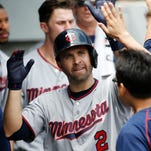 Minnesota Twins' Brian Dozier, a former Southern Miss star, celebrates with teammates in the dugout after hitting a solo home run Thursday.