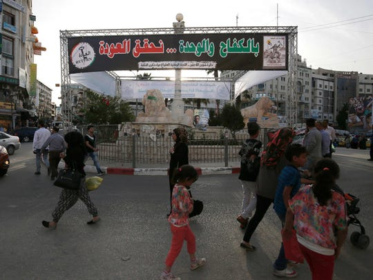 Palestinians walk past a banner marking the 68th anniversary