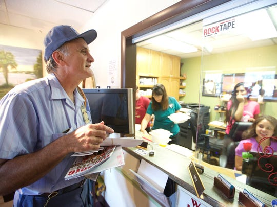 Tim Kelly chats with some of the women at Magnolia Chiropractic, one of the business on his route in Tallahassee where he has been delivering packages since 1983. Kelly is set to retire from his Post Office job this week.