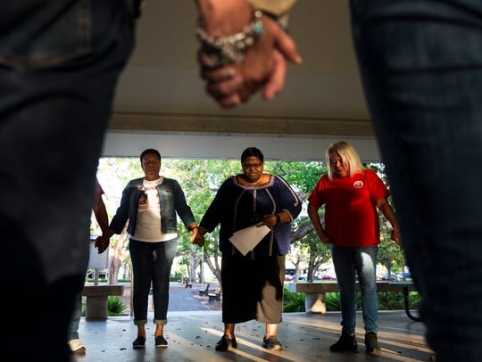 Seena Washington, center, leads a prayer alongside Marcia Williams, left, the mother of Collier County missing person Terrance Williams, and Monica Caison, right, founder of the Cue Center for Missing Persons, at Cambier Park in Naples on Wednesday, Oct. 25, 2017, during a ceremony to remember missing people.