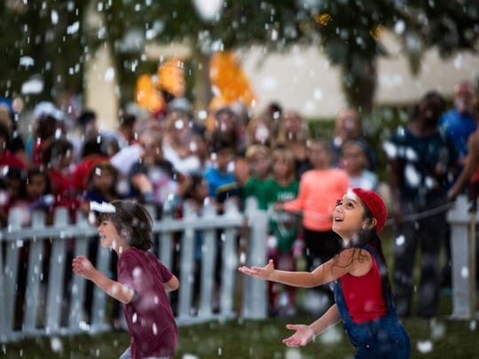 Mia Echezarreta, 6, holds out her hand to feel man-made snow during the Holiday in the Park event at Riverside Park in Bonita Springs, Fla., on Tuesday, Dec. 5, 2017.