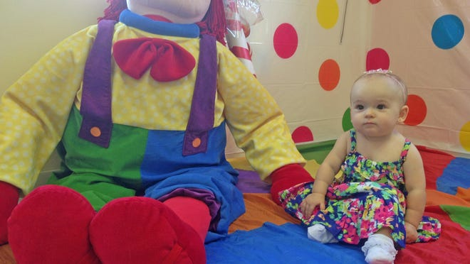 Isabella has her photo taken with Gymbo the Clown before to the Candy Land-themed Parachute Prom at Gymboree.