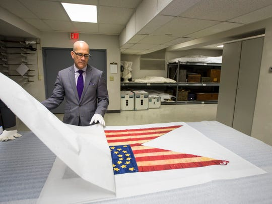 Michael Telzrow, director of the Wisconsin Veterans Museum, unveils a recently acquired Civil War guidon. The guidon, or flag, from the 2nd Wisconsin Cavalry Regiment, was donated by a great-granddaughter of a corporal who fought in the war.