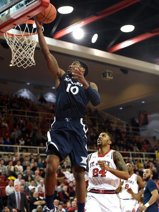 Xavier guard Remy Abell (10) drives the ball to the basket past St. John's forward Ron Mvouika (24) during the first half of an NCAA college basketball game on Wednesday, Jan. 6, 2016 in New York. (AP Photo/Kathy Kmonicek)