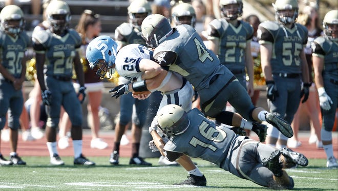 Clarkstown South defenders Mike Margolis (16) and Kyle Samuels (4) tackle Suffern Dan Sharp (25) during a football game at Clarkstown South High School on Saturday, September 17, 2016.  Clarkstown won 30-0.