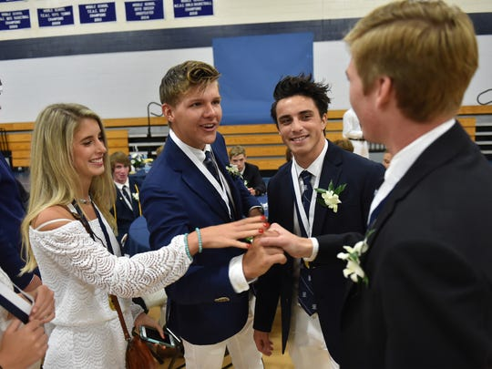 St. Edward's School graduates (from left) Julie Young, Donald Meadows III, Juan Torres, and Parker Hammond prepare for their class of 2018 commencement ceremony at the Waxlax Center for the Performing Arts on Saturday, May 26, 2018, in Vero Beach.