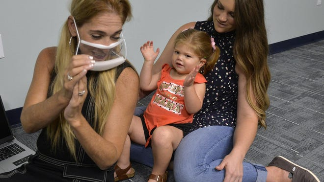 Jordyn Sitzler, 2, sitting in her mother's Ashlee lap, claps when she hears her teacher Tracy Edenfield clap. Edenfield wears a clear face mask because children in speech and language development need to see facial expressions and watch the mouth of the teacher.
