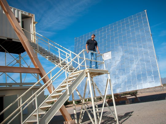 White Sands Missile Range electronics engineer Jose Enriquez stands in front a heliostat, a 40-foot wide, 36-foot high perpendicular plane of 180 two-foot by two-foot-square mirrors which will help focus sunlight onto a sample of the mineral williamsite serpentine as part of a space asteroid mining test at WSMR on Friday.