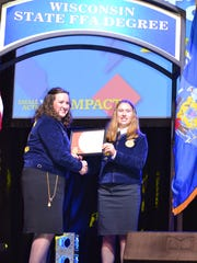 Wisconsin State FFA President Brenna Bay presents the Wisconsin State FFA Degree to Emily Schwanke of Waupun FFA during the 88th Wisconsin FFA Convention. 332 FFA members received the State FFA Degree, the highest degree that members can receive on the state level.