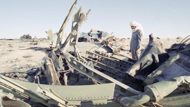 A Niger desert guide is framed by the debris of the UTA DC-10 airliner Sept. 24, 1989.