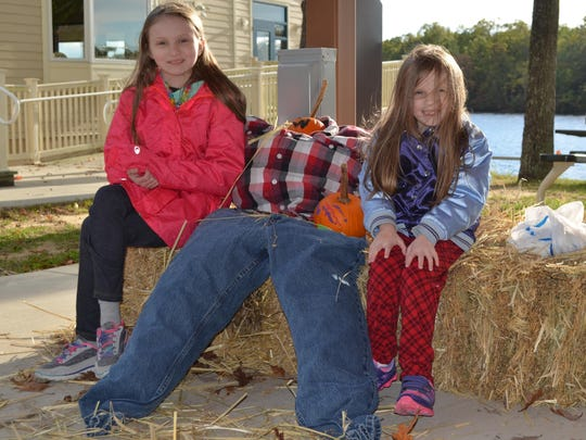 Kessa Baldish, 9, and Nadia Baldish, 6, of Mays Landing sit next to the scarecrow they made at the pumpkin festival that was presented by the Atlantic County Division of Parks and Recreation on Saturday at Lake Lenape East catering hall.