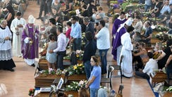 People attend a funeral service for victims of the