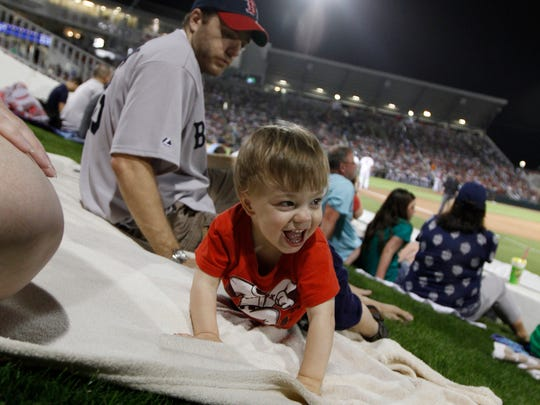 George Wespi, 18 months, smiles at neighbors while playing on a blanket at Hammond Stadium Thursday in Fort Myers.