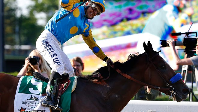 Victor Espinoza reacts after crossing the finish line with American Pharoah (5) to win the 147th running of the Belmont Stakes horse race at Belmont Park, Saturday, June 6, 2015, in Elmont, N.Y. American Pharoah is the first horse to win the Triple Crown since Affirmed won it in 1978.  (AP Photo/Kathy Willens)