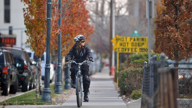 Photo from 2010: Reno Code Enforcement Officer Cindi Gil-Blanco rides her bike through downtown Reno checking on code enforcement issues along the way.