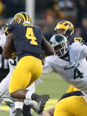 Michigan State's Malik McDowell tackles Michigan's De'Veon Smith during the third quarter Saturday in Ann Arbor.