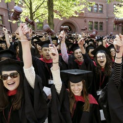 In this May 29, 2014 photo, graduates from the Harvard Law School wave gavels and cheer during Harvard University commencement ceremonies, in Cambridge, Mass.