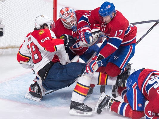 Florida Panthers' Jaromir Jagr is taken out from in front of Montreal Canadiens goalie Mike Condon by Canadiens' Torrey Mitchell during the second period of an NHL hockey game Tuesday, March 15, 2016, in Montreal. (Paul Chiasson/The Canadian Press via AP)