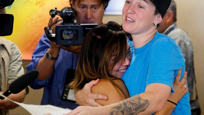 Samantha Getman, right, and Victoria Quintana embrace as they receive their marriage license at the Denver Clerk's office on Thursday. They were the first couple to be married in Denver, after clerk Debra Johnson began issuing licenses to same-sex couples on Thursday.