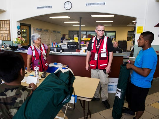 Bryan Hartmann, a Red Cross shelter manager, second from right, talks with a family preparing to check out at the emergency shelter at the Estero Community Park Recreation Center on Sunday, Sept. 24, 2017.