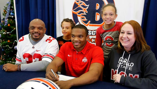 Blackman football player Master Teague, center, signs to play football for Ohio State as he is surrounded by his family (L to R) Corey Teague, Myles Teague, 8, Master Teague, Molly Teague, 9 and Emily Teague, on Wednesday, Dec. 20, 2017, in the Blackman library.