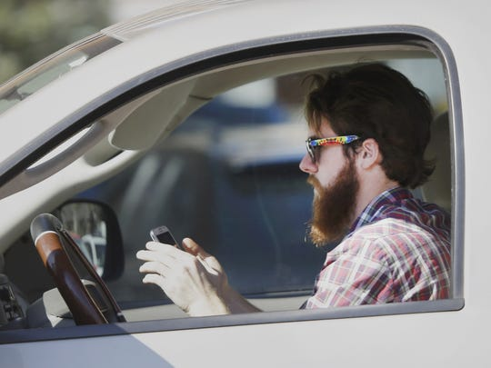 A man works his phone as he drives through traffic. North Carolina is stepping up enforcement of texting and driving rules.