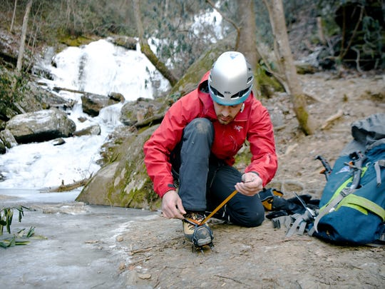 Anthony D'Ercole straps his crampons to his feet as he prepares to climb the iced-over Catawba Falls in Old Fort on Friday, Jan. 5, 2018. The ice-climbing devices help climbers kick into the ice and keep their footing as they climb.