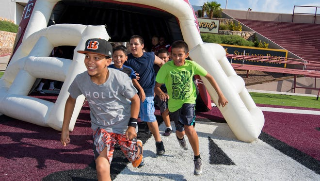 11 year old Keshaun Golden leads the pack out of the giant Aggie football helmet at the New Mexico State football team's fourth annual kid's clinic Saturday at Aggie Memorial Stadium.