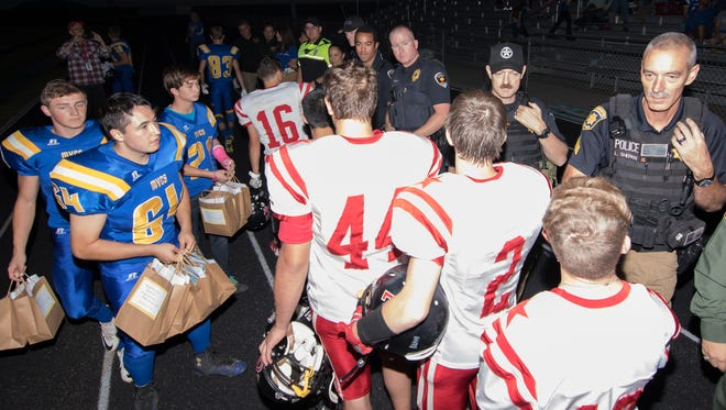 Members of both Mesilla Valley Christian School and Tatum football team senior players shake hands and offer the law enforcement personnel an appreciation gift before the start of their game on Friday night, Sept. 30, 2016.