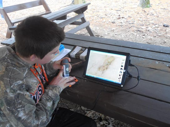 A 4-H member uses technology to learn about the environment.