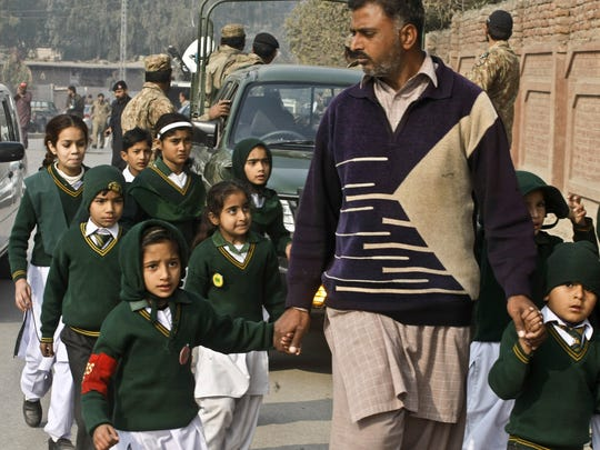 A plainclothes security officer escorts students rescued